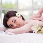 Relaxed woman with flowers in spa center enjoying massage