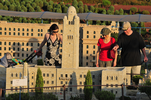 Visitors stands near a miniature of the Y.M.C.A. tower in Jerusalem at Mini Israel a miniature park located near Latrun, Israel in the Ayalon Valley.