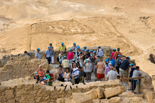 MASADA, ISRAEL - OCT 14, 2014: Tourists on top of the rock Masada in Israel, with a Roman camp on the background